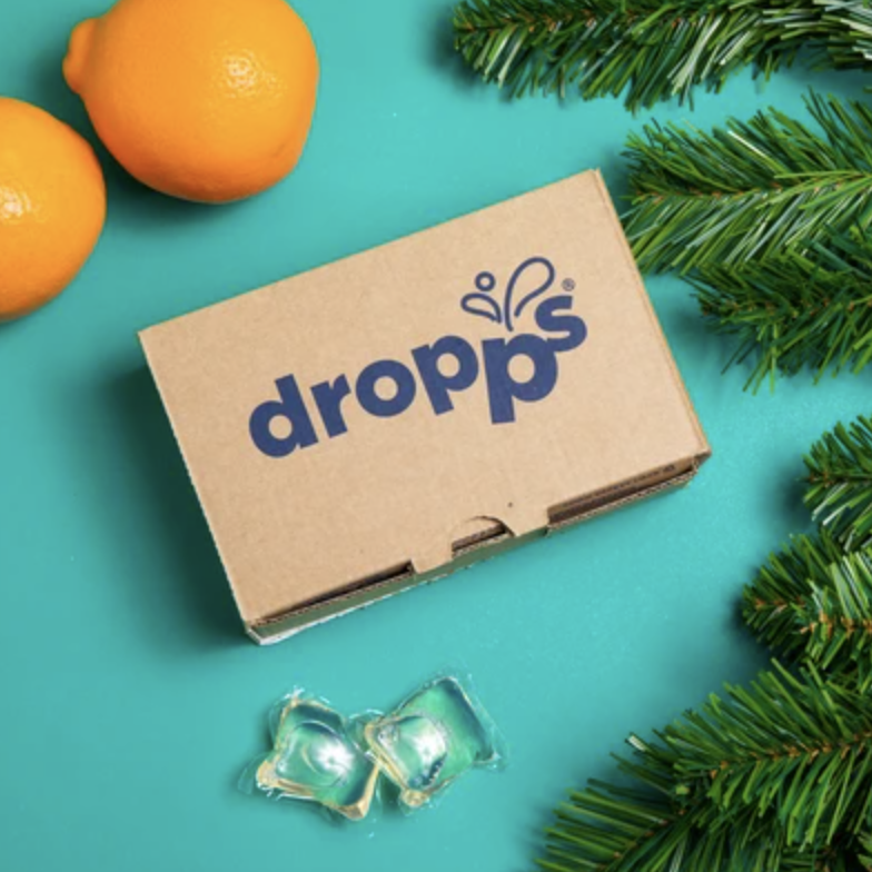 A box of Dropps biodegradable laundry detergent pods next to two oranges and pine tree leaves