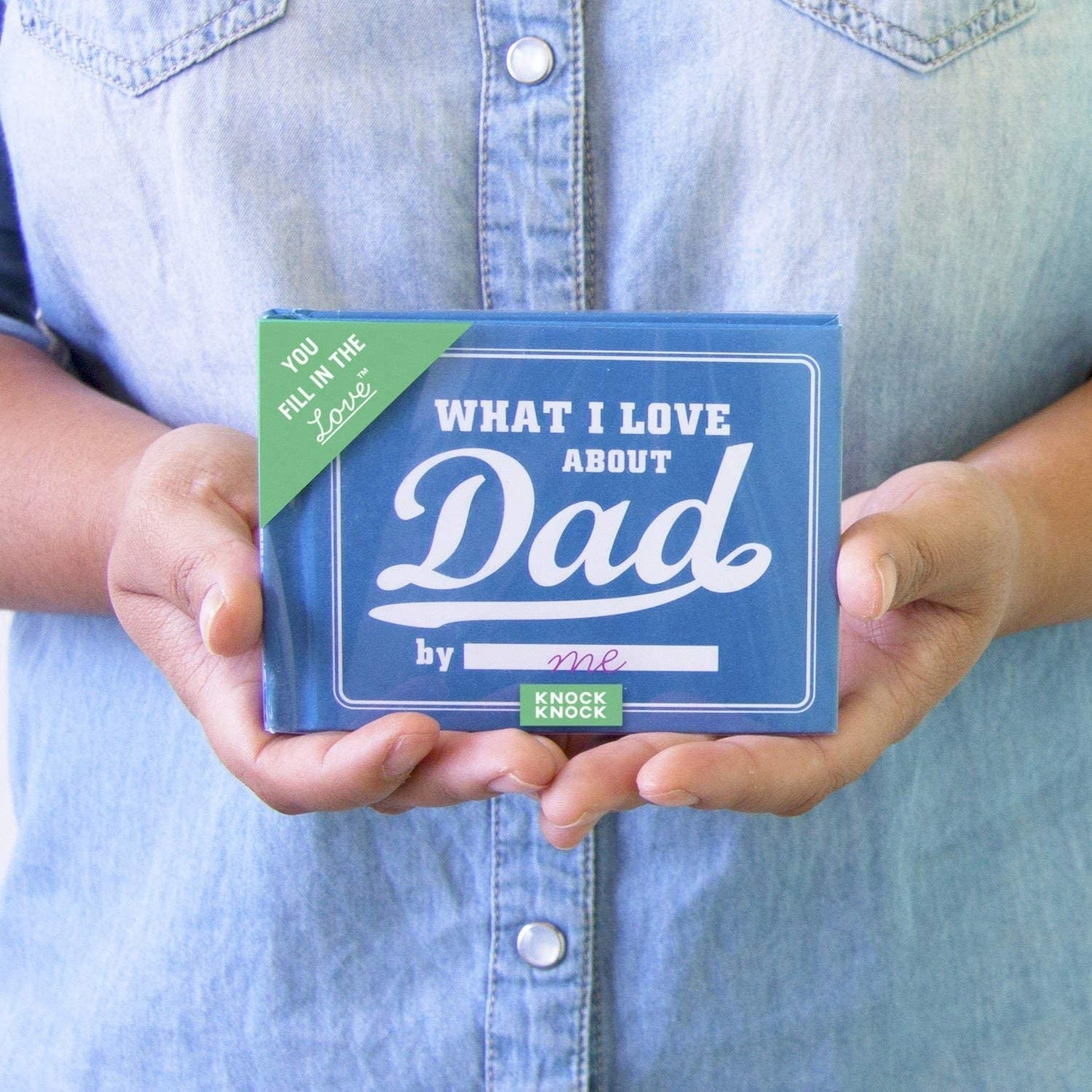 Someone holding up a book called What I love About Dad by: Me