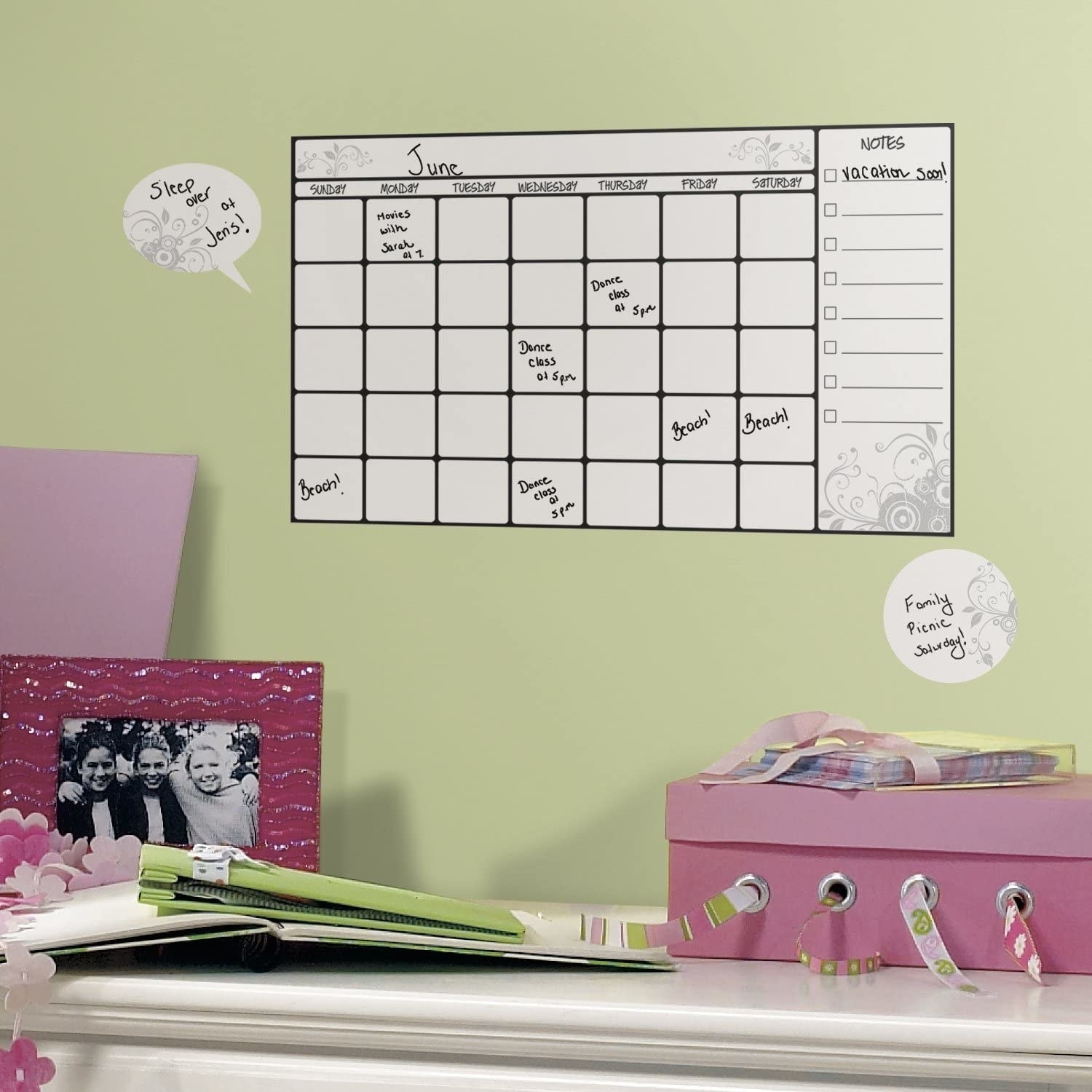 A dry-erase decal calendar on a wall with text written on the days in marker