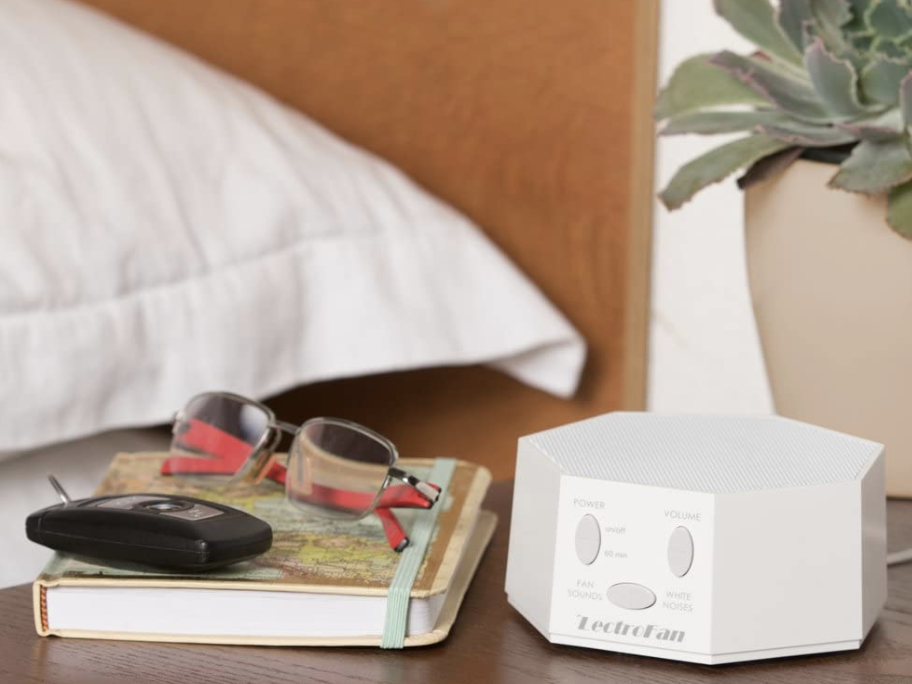The white noise machine on a bedside table