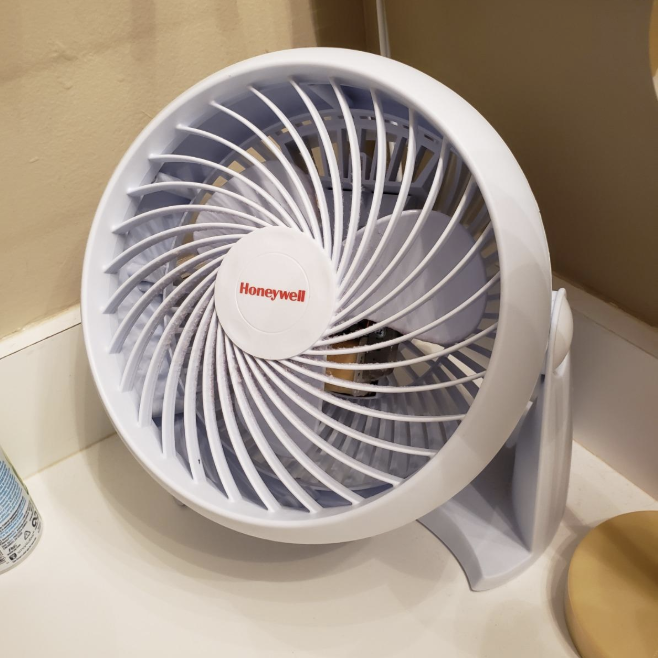 A white circular personal fan on a counter