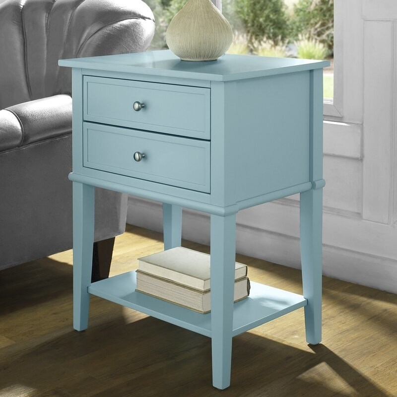 a light blue end table with two drawers and a bottom shelf