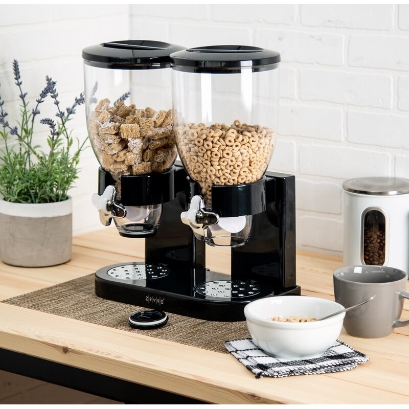 two plastic cannisters filled with cereal placed into a black contraption that'll let you dispense a standard size portion. There's also a crumb collecting tray underneath