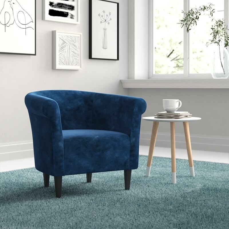 a velvet blue chair with short plastic legs and a U-shaped back