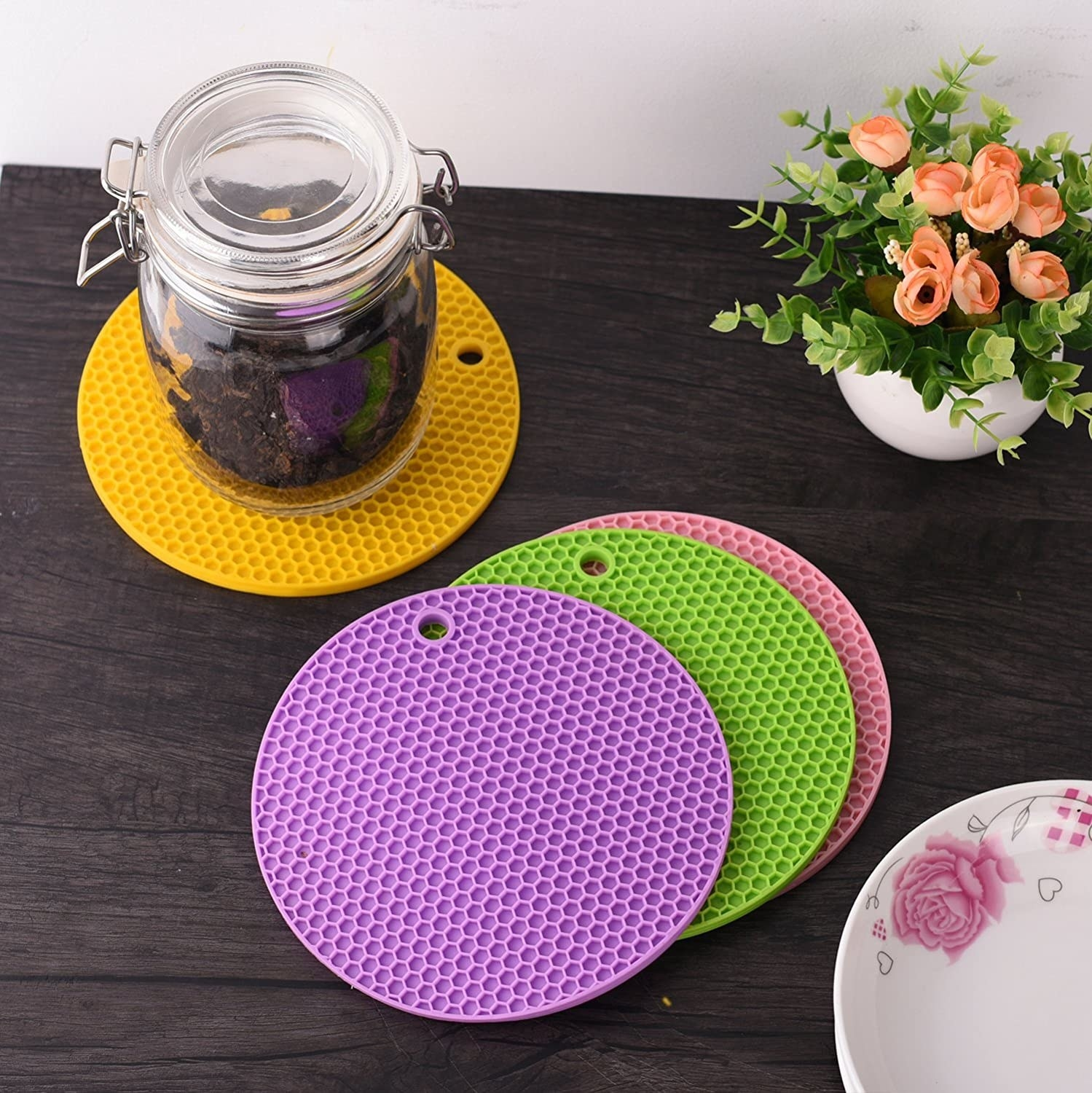 A set of four circular trivet mats in purple, green, pink, and yellow