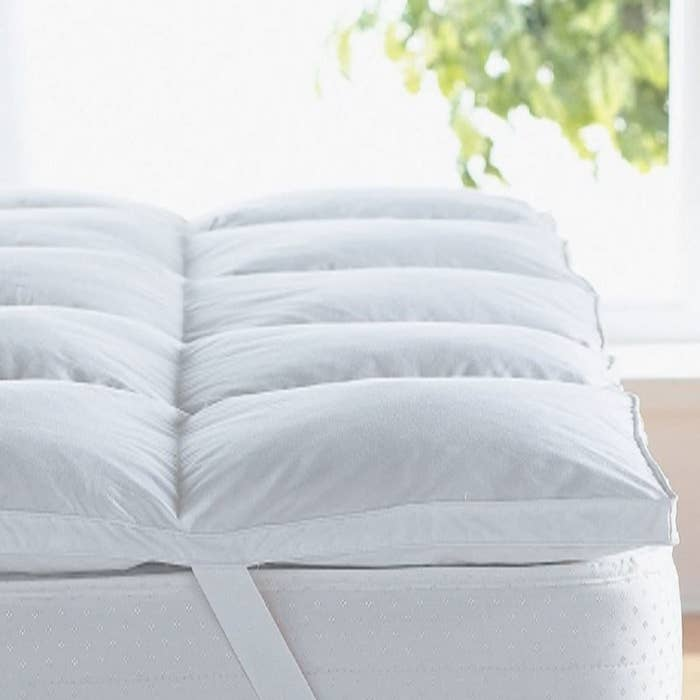 Close up of the pad on a mattress, showing two rows of square baffle boxes that are fluffiest in the middle