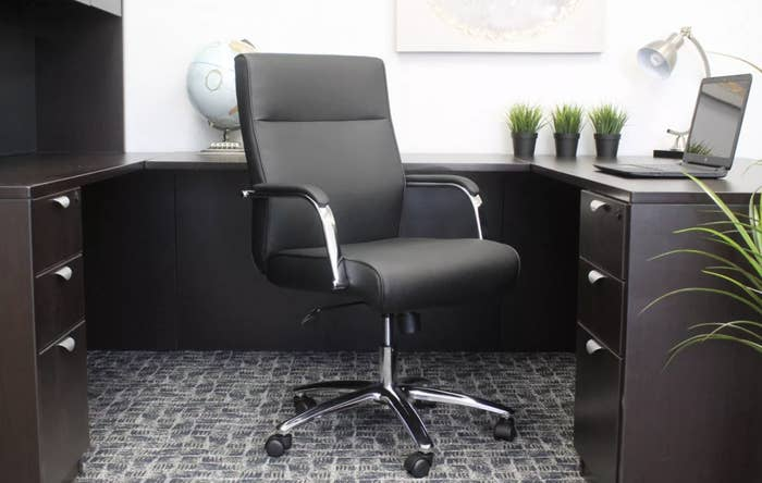 A black desk chair with metal legs and armrests on five caster wheels