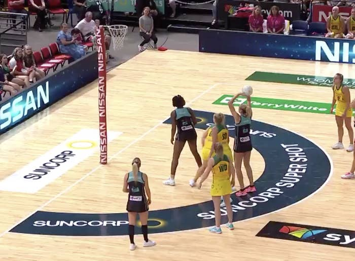 A netball player taking a shot from inside the two-point zone