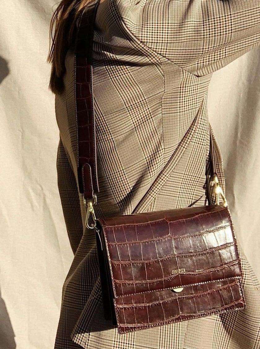 model wearing brown flap bag