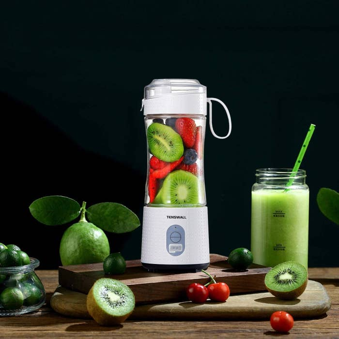 A white blender with clear plastic up filled with strawberries blueberries, and kiwis