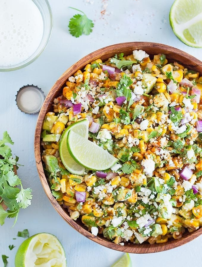 A big bowl of Mexican street corn salad topped with cilantro, cheese, red onion, avocado, and lime wedges.