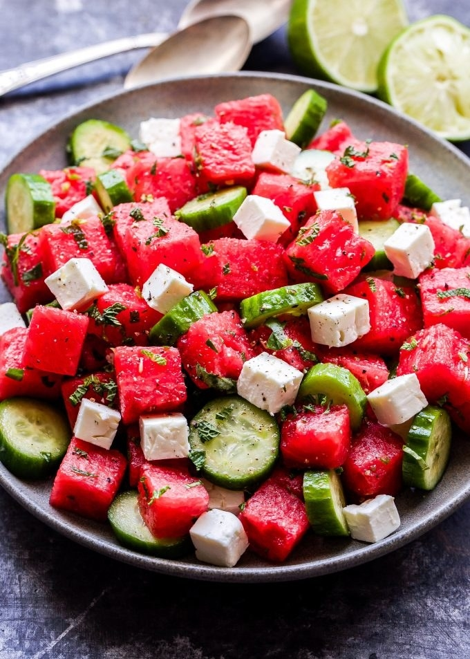 A salad with fresh watermelon, cucumber, chunks of feta, fresh basil and mint.