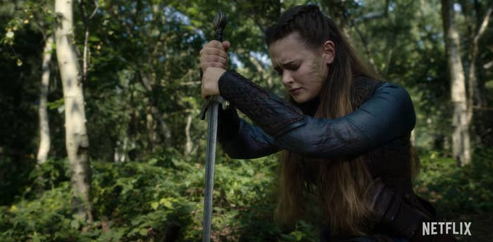Katherine Langford as Nimue kneeling with the sword