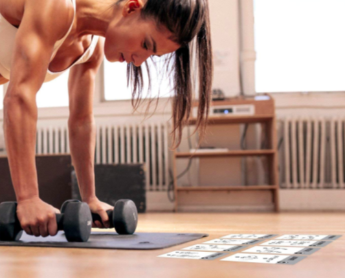 Model tests out exercise card deck with two black dumbbells