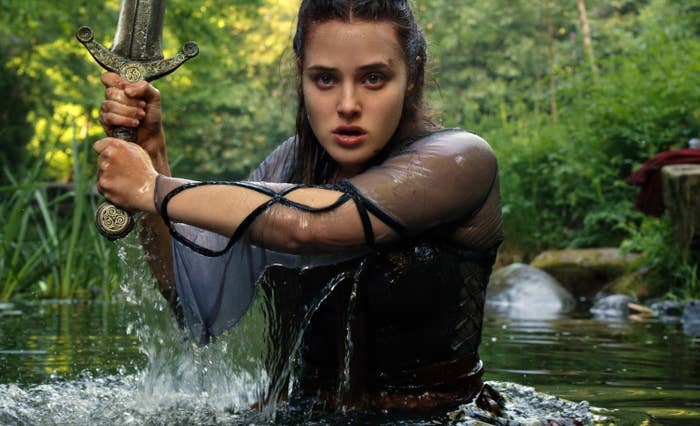 Katherine Langford as Nimue coming out of a lake wielding a sword