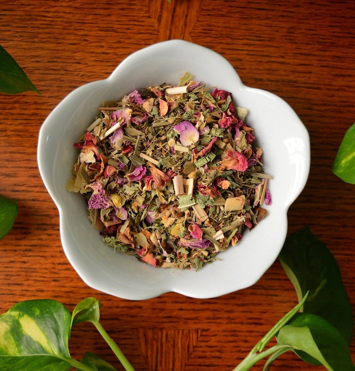 a bowl of loose tea with dried pink petals in it