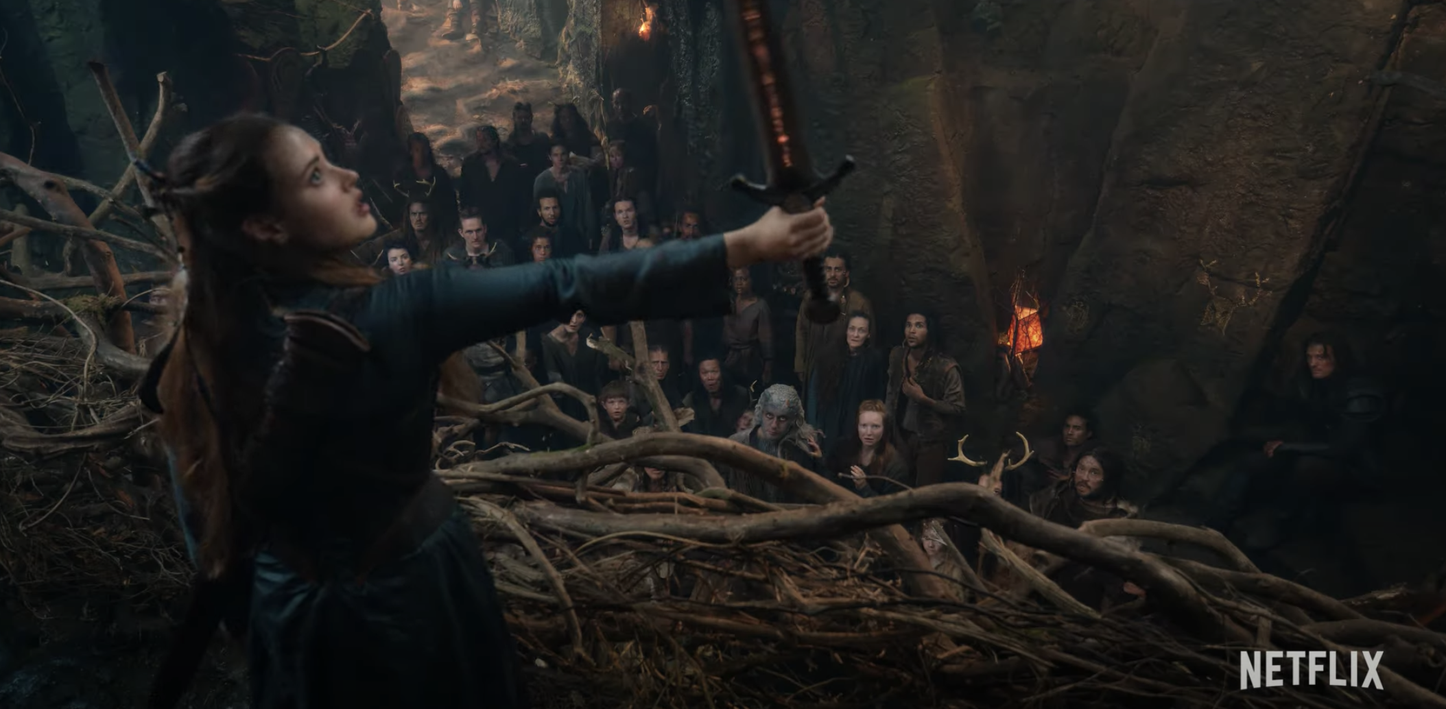 Katherine Langford as Nimue wielding the sword in front of a crowd