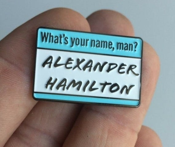 """An enamel pin shaped like a nametag that says """"What's your name, man? Alexander Hamilton"""""""