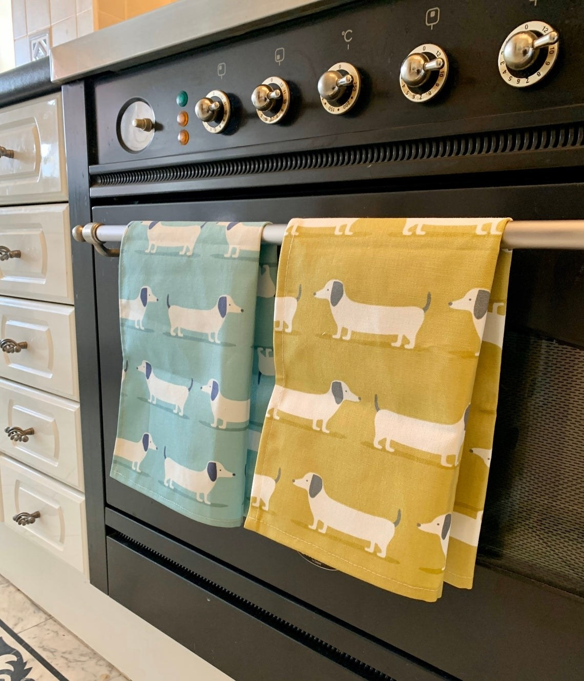 two tea towels in blue and yellow with white dogs on it