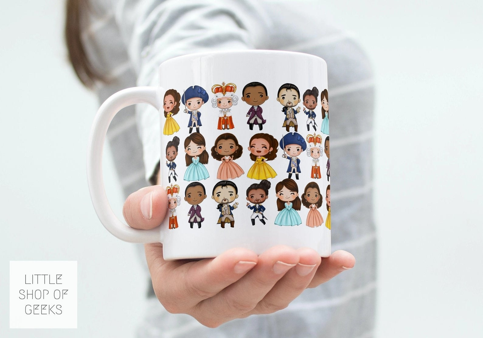 A white mug with the Hamilton characters as cartoons on it