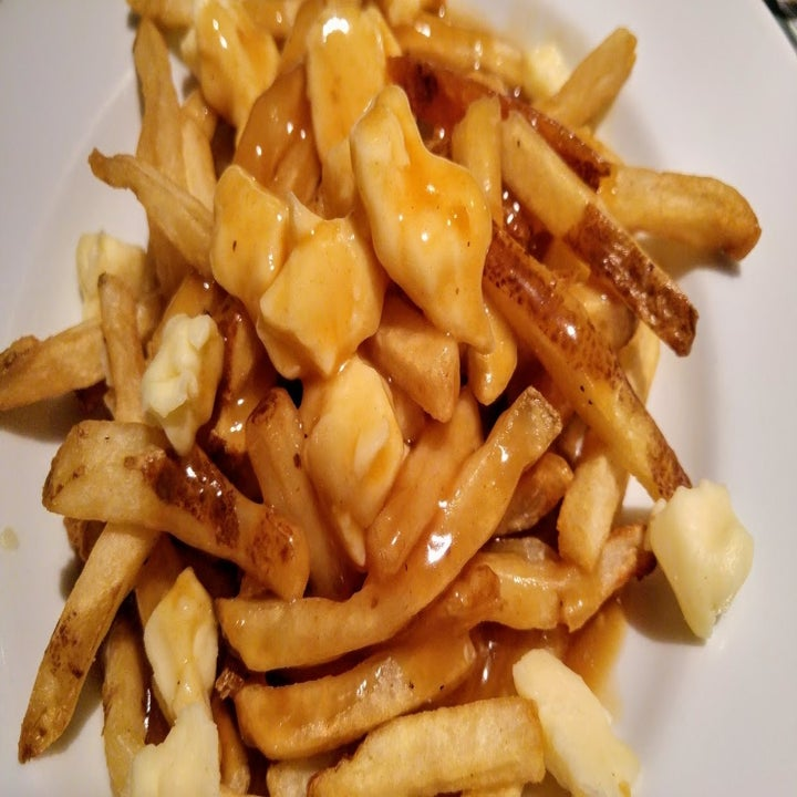 Poutine covered with gravy and cheese curds sit upon a white plate.