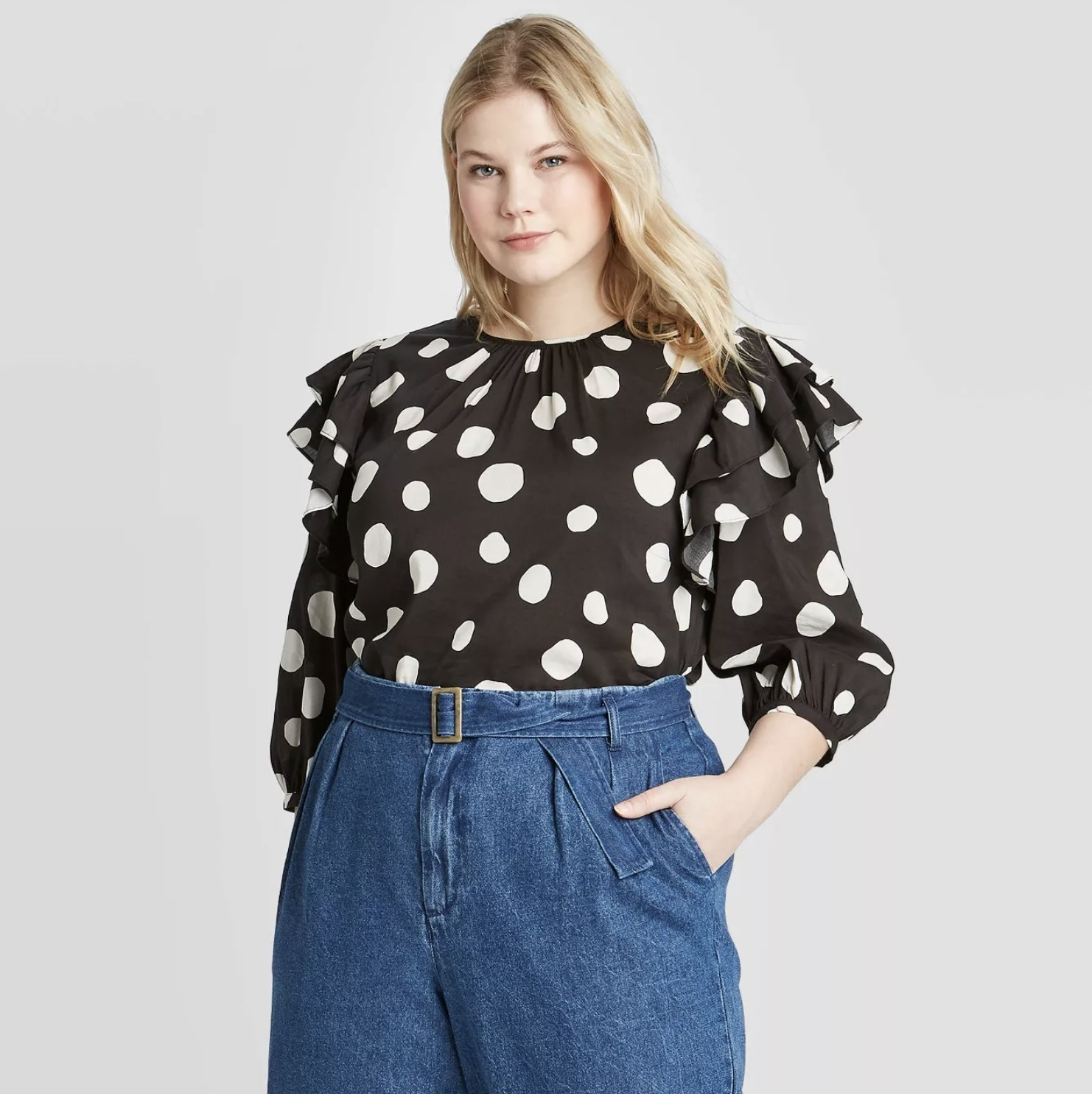 A model wearing a black long sleeve top with white polka dots