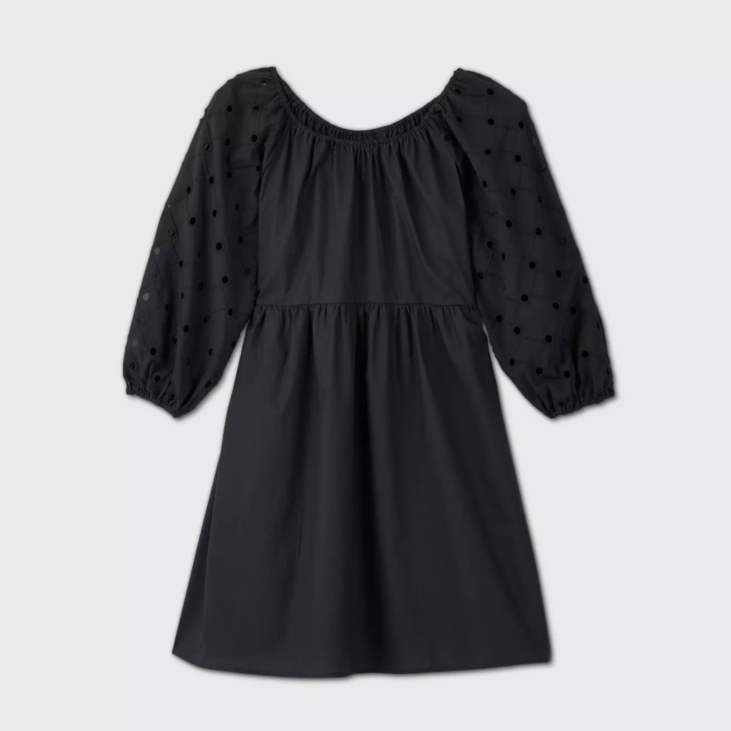 A black baby doll dress with a wide neck and black dots on the sleeves
