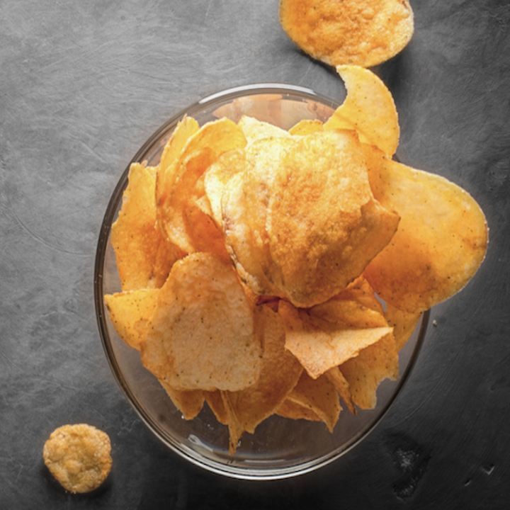 A clear bowl sits upon a gray table, and the bowl is filled with chips that look like barbecue chips but are meant to be ketchup chips.