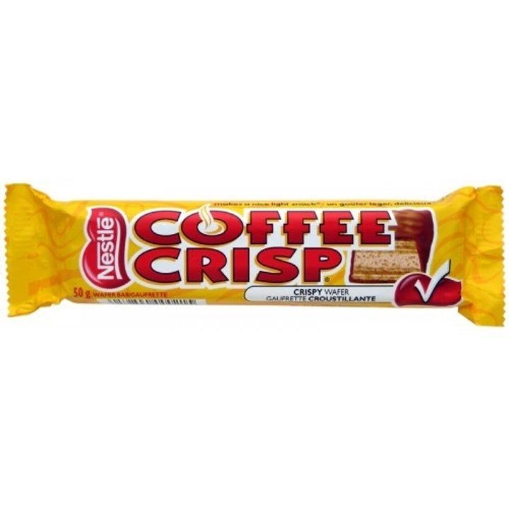 A Coffee Crisp chocolate bar wrapper in front of a white background. The wrapper is yellow with red lettering, with a photo of a coffee crisp bar on it. The bar looks like a larger Kit Kat.