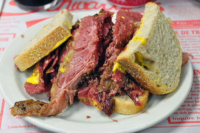 A close-up of a Montreal-style smoked meat sandwich, which kind of looks like pastrami, and is covered in mustard. It sits up on a white glass plate, on top of a red-and-white printed diner menu.