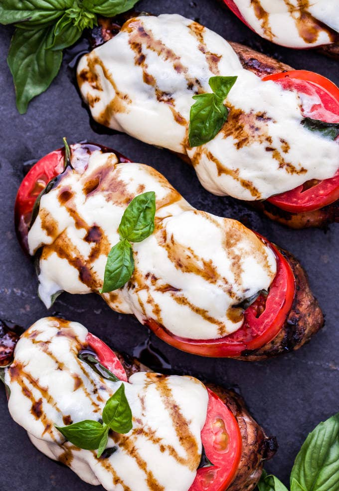 Three pieces of balsamic grilled chicken topped with sliced tomatoes, melted mozzarella, basil, and balsamic glaze.