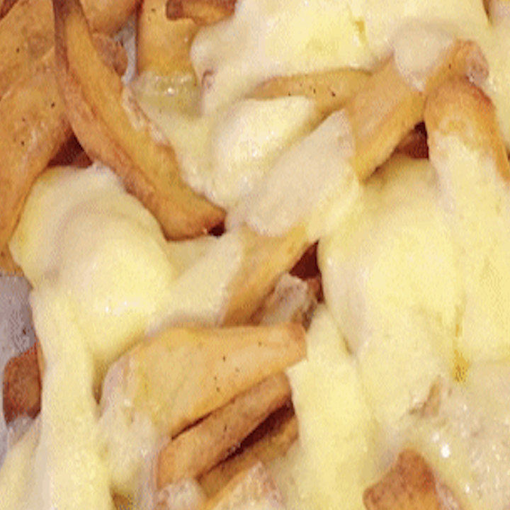 Close-up of French fries covered in melted cheese, called poutine.