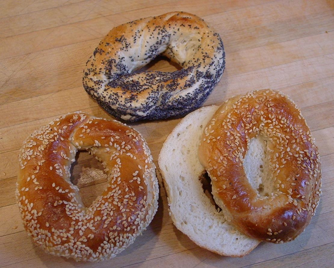 A close-up of three Montreal-style bagels sit on top of a wooden table. Montreal-style bagels look thin but are covered in sesame seeds and poppy seeds.