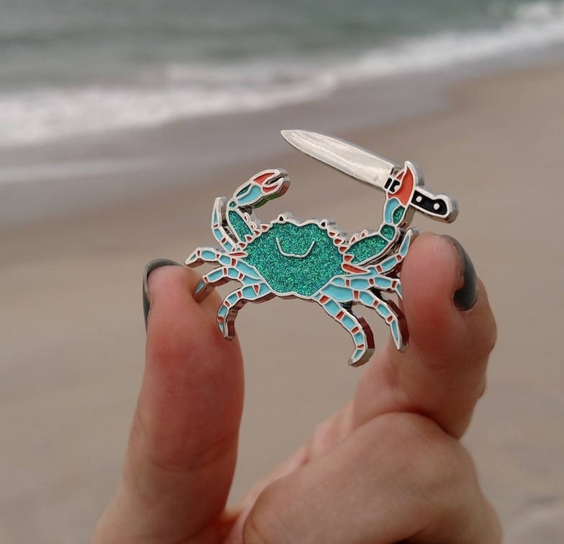 A person holding the enamel Stabby Crab pin.