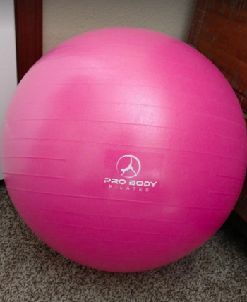 Reviewer shows pink exercise ball in a corner of their living room