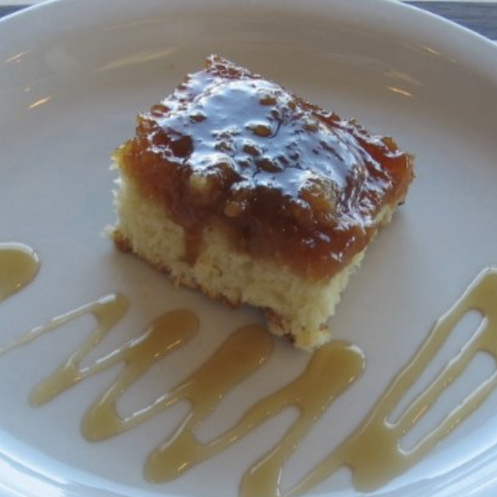 A yellow cake square with a layer of maple syrup and caramel on top, sits atop a white plate. Maple syrup or caramel is drizzled on the plate.