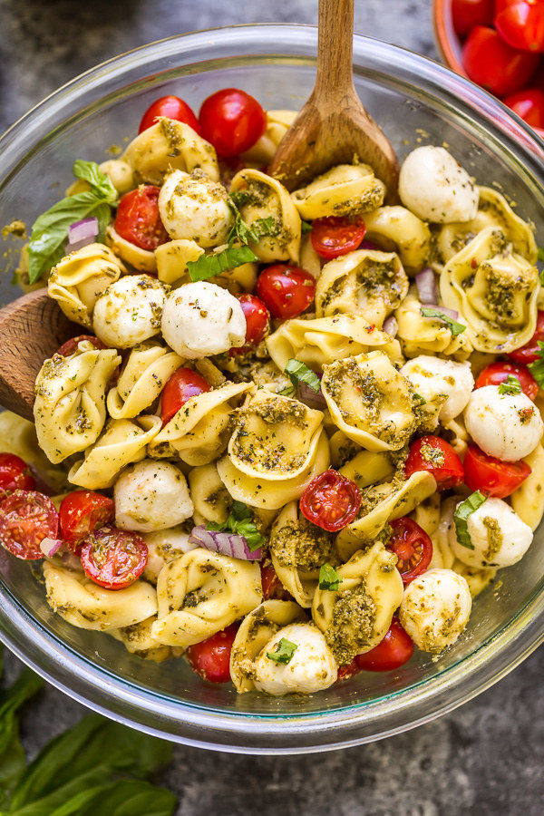 A big bowl of tortellini pasta salad with mozzarella, tomato, and pesto.
