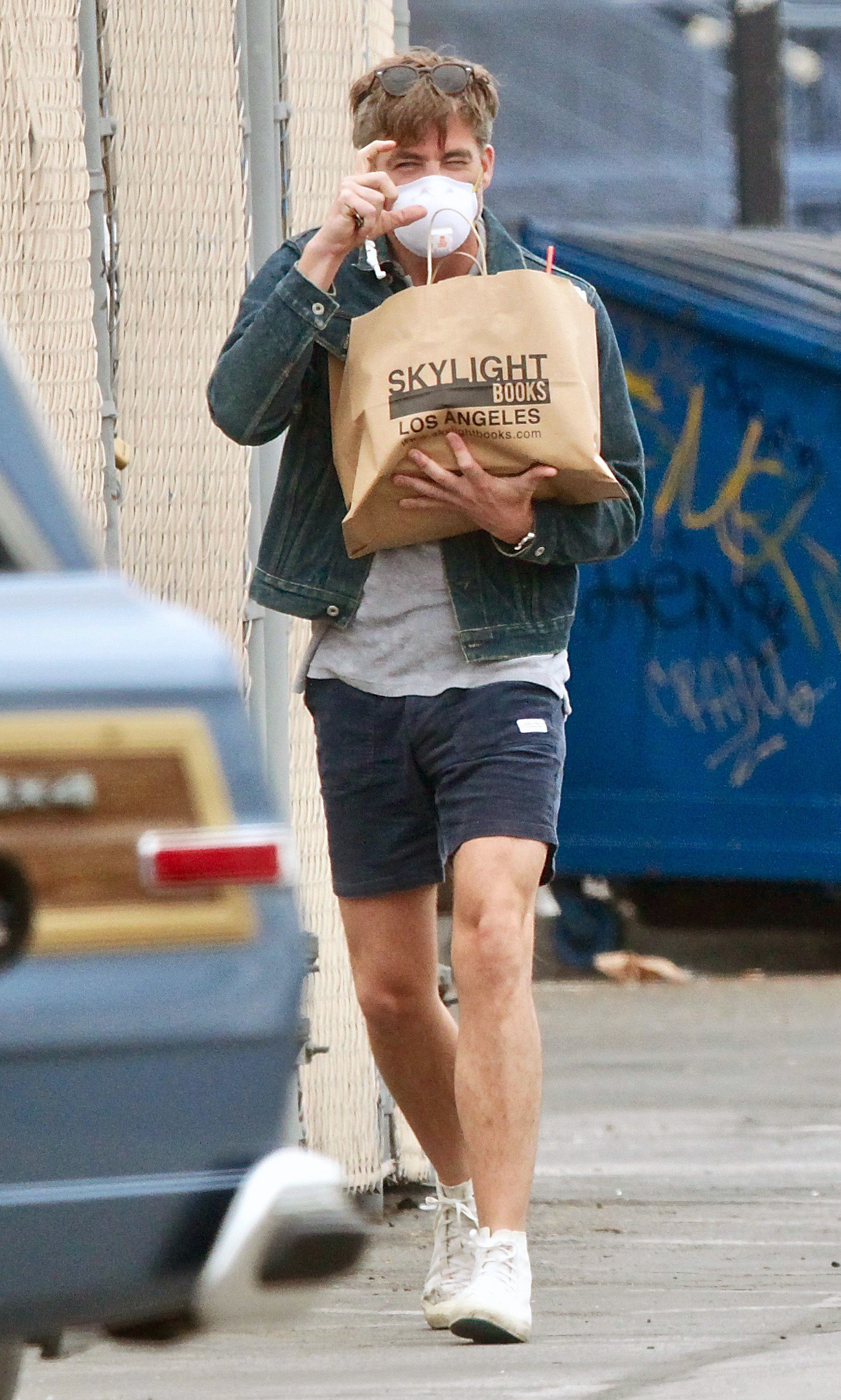 Chris Pine walking in shorts and a t-shirt with a jean jacket, a medical mask, and a brown paper bag of books