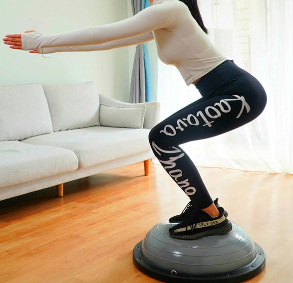 Model uses gray balance ball trainer to do a squat in her living room
