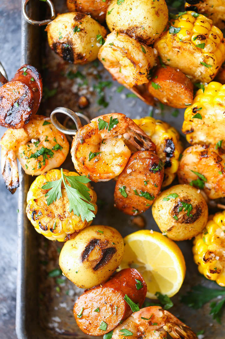 Skewers with shrimp, sausage, corn, and fresh herbs just off the grill.