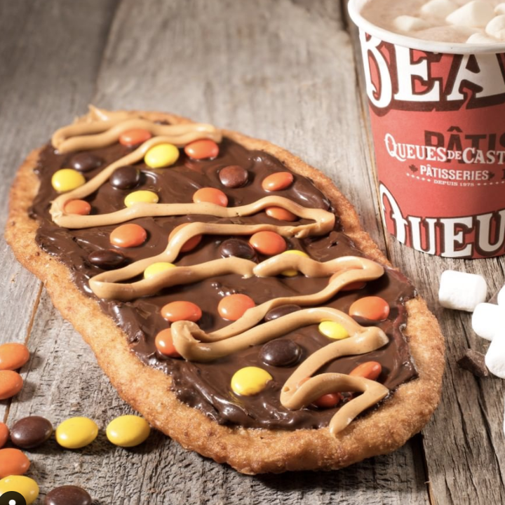 A beaver tail, which looks like a dessert flatbread, sits on a wooden table. It is covered in chocolate, topped with Reese's Pieces and a peanut butter drizzle.