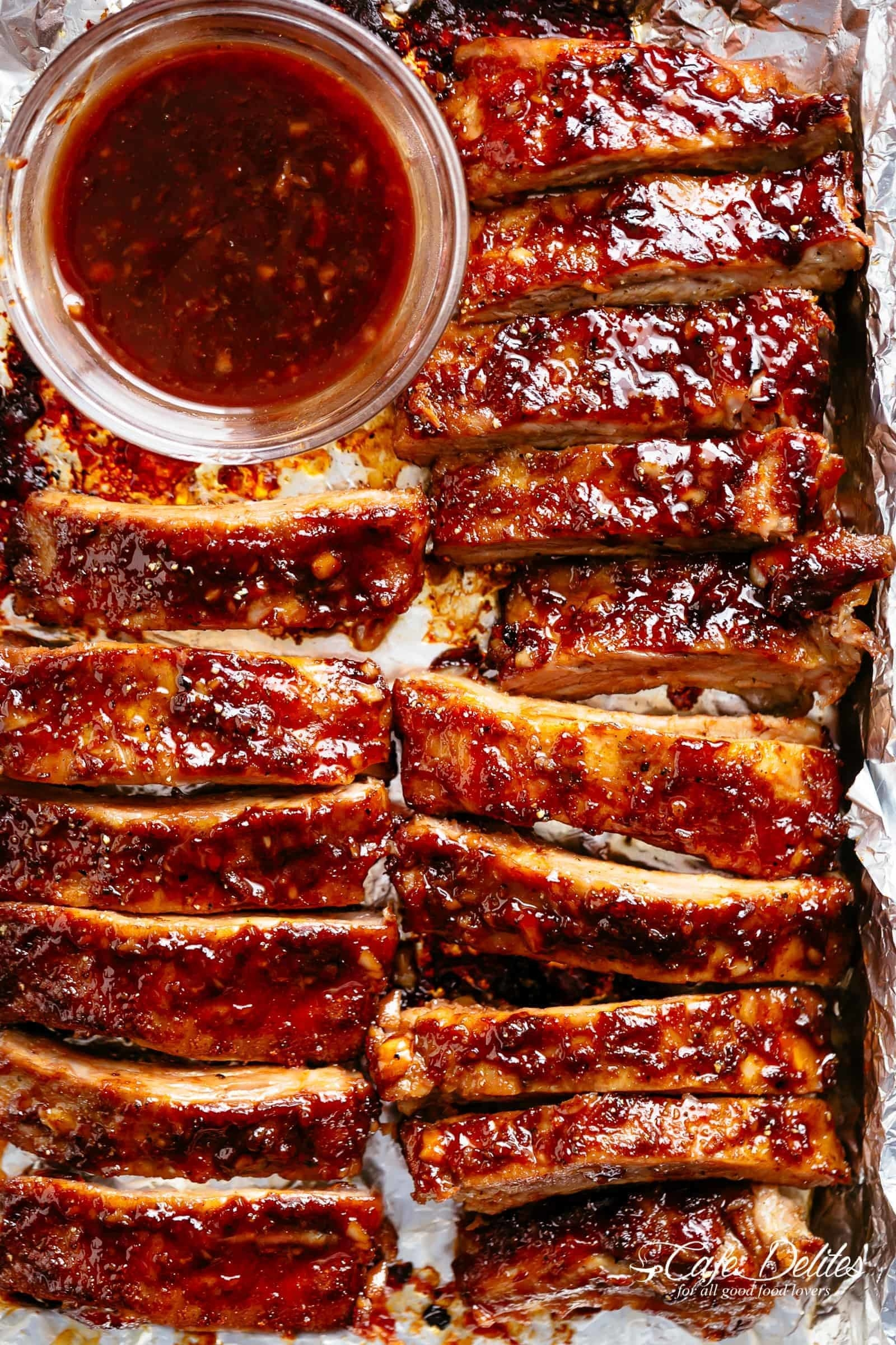 A dozen-or-so ribs brushed with barbecue sauce on a foil-lined baking sheet.