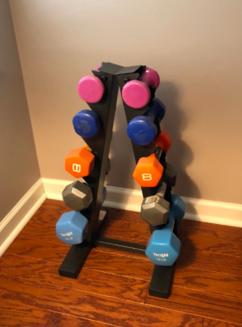 Reviewer uses black dumbbell weight rack to hold their eight and five-pound weights against a wall