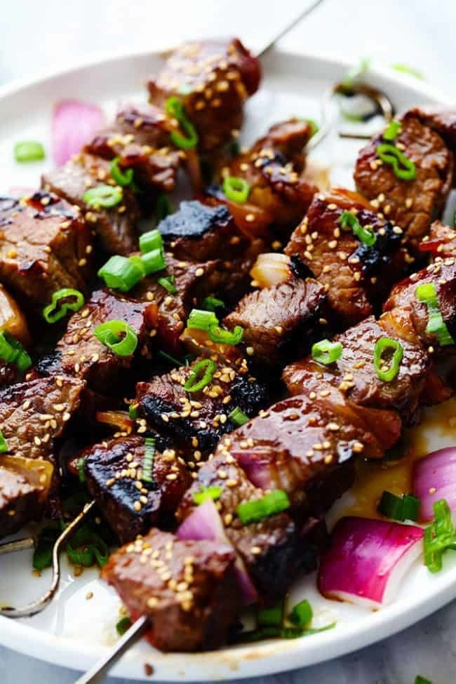 Skewers of grilled steak marinated in a soy and garlic sauce with red onions and fresh herbs.