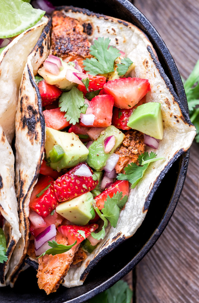 An up-close shot of a tortilla filled with grilled salmon and a slaw made of avocado, strawberry, red onion, and cilantro.