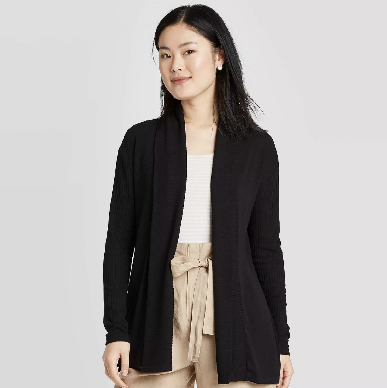 A model wearing an unbuttoned black cardigan that hits at the hips