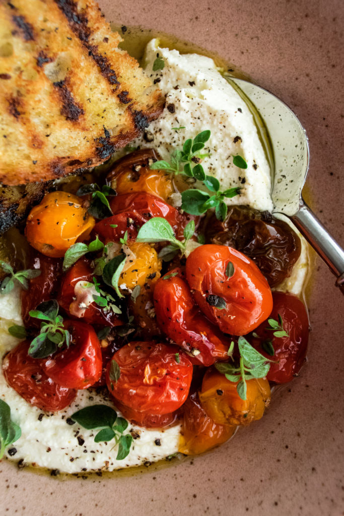 A close-up shot of whipped feta cheese with juicy, blisrered tomatoes, fresh herbs, and bread on the side.