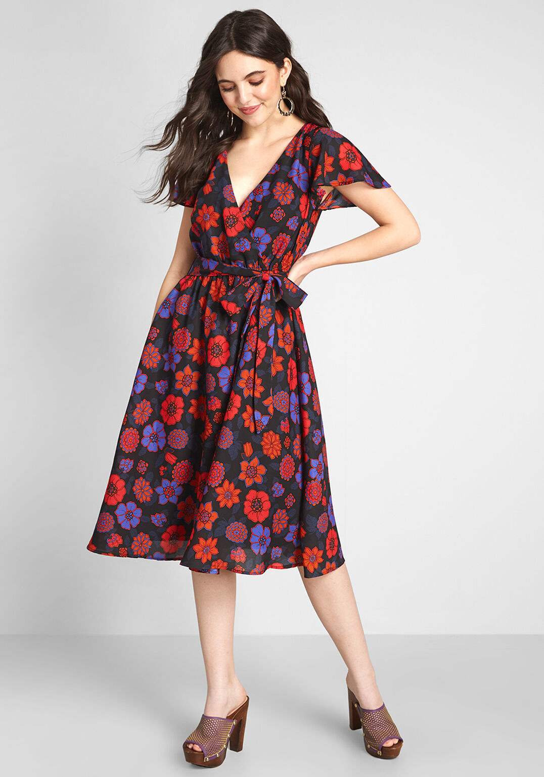 Model wearing the dress, printed with red, orange, and purple flowers