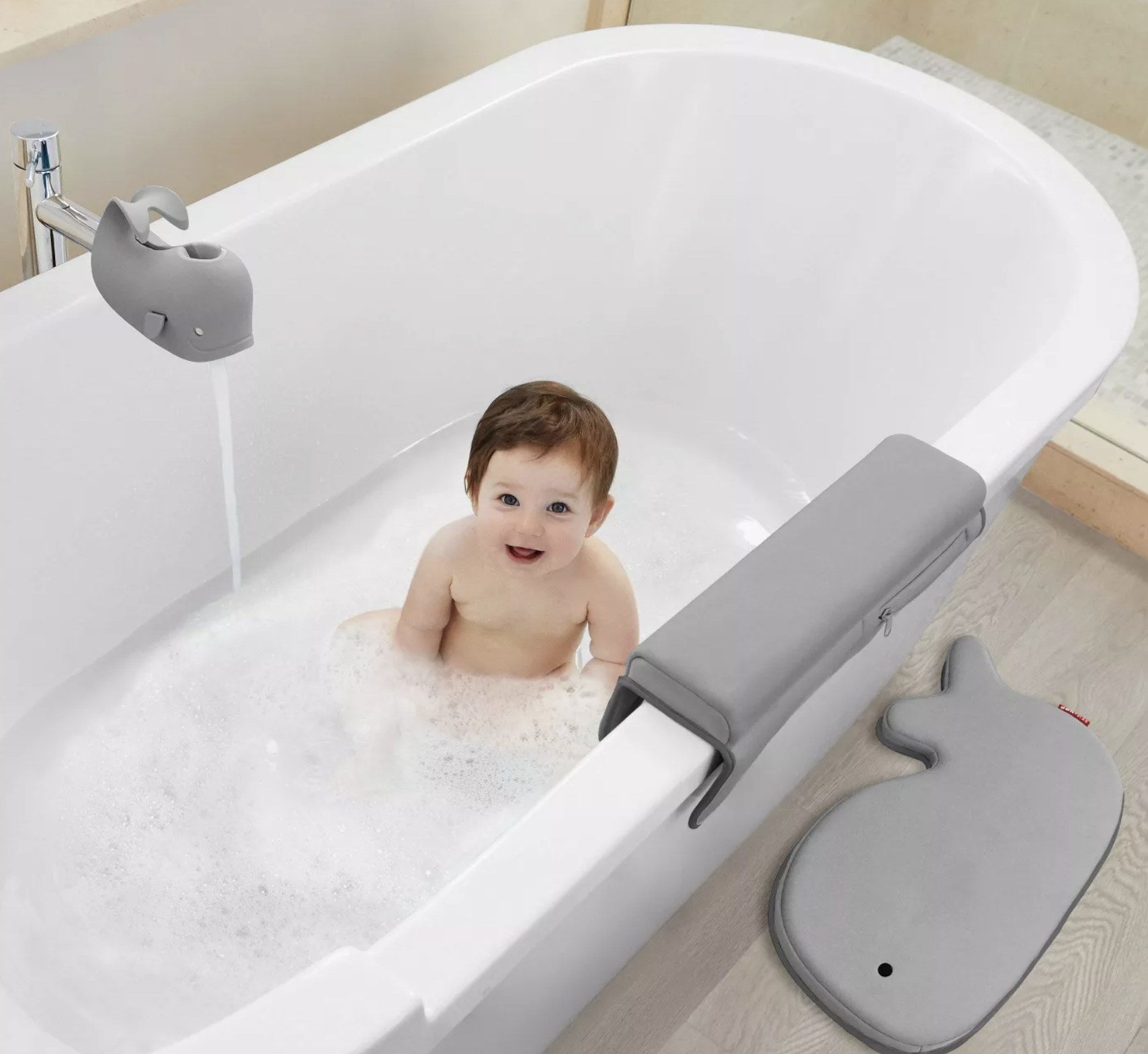 A toddler model in with gray whale bath mats and spout cover