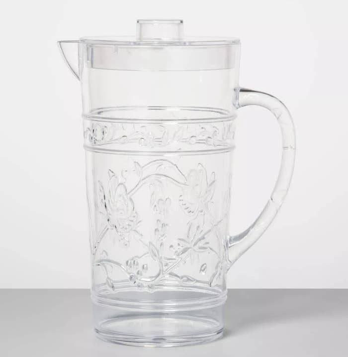 A glass pitcher with a lid and floral designs